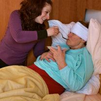 caregiver feeding her sick patient