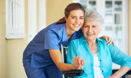 caregiver and senior woman on wheelchair smiling