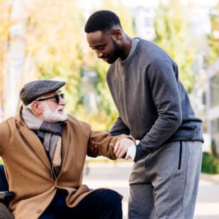caregiver assisting his patient standing up