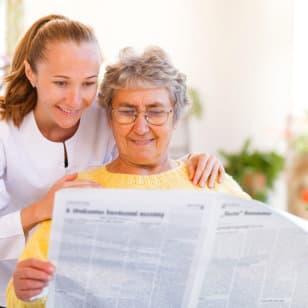 senior and caregiver reading newspaper