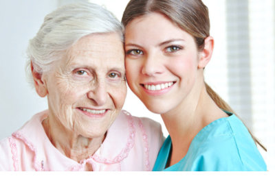 smiling caregiver embracing happy senior women in nursing home