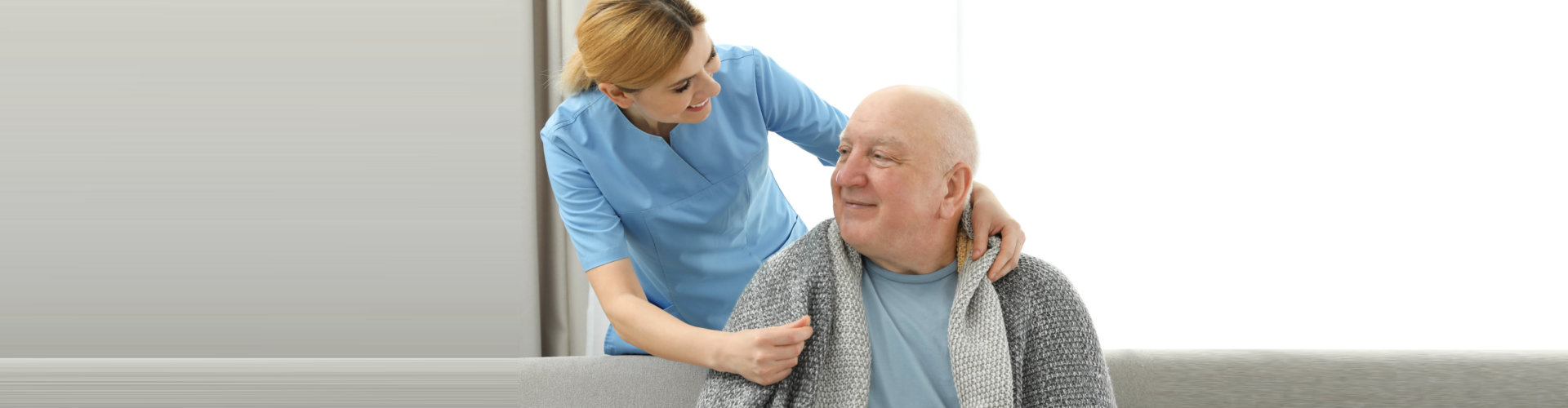caregiver checking her senior patient on couch