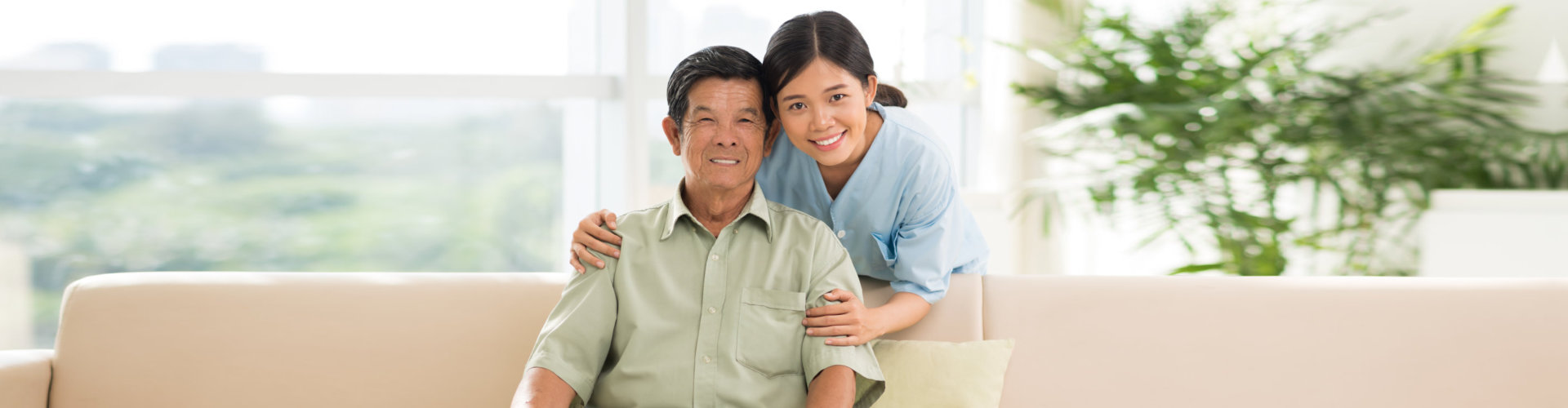 caregiver and senior on couch smiling